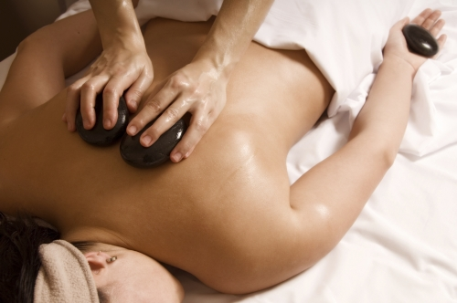 Therapist giving a hot stone massage to client